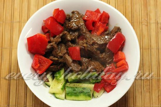 Переложить мясо в миску, добавить огурцы и сладкий перец