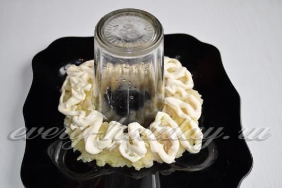 На блюдо поставим стакан. Первым слоем выложим картофель, как бы вкруговую стакана. Промажем картофель майонезом