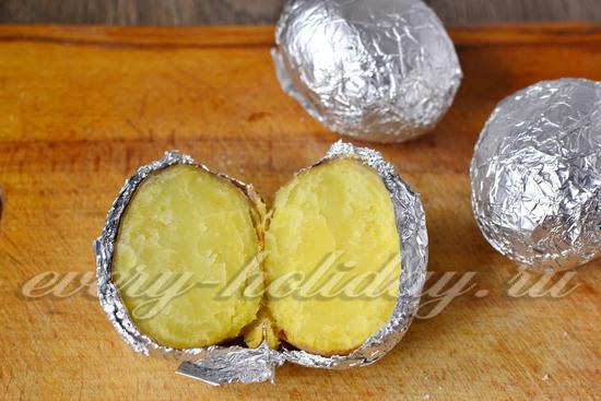 Далее достаём готовый картофель и разрезаем его пополам
