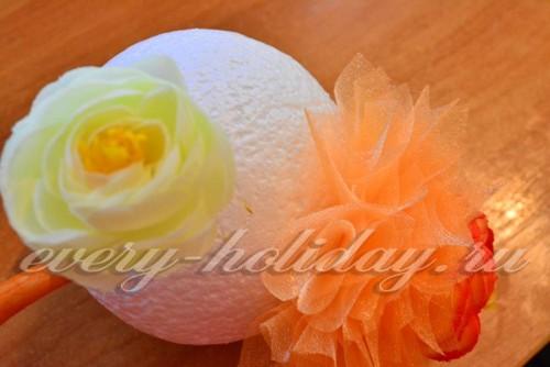 Затем берем текстильные цветочки и приклеиваем по одному к шару. Каждый цветочек вокруг обклеиваем «торцовками».