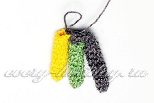 Довяжем ряд до места, где приложим желтое перо вслед за зеленым и прификсируем его парой соединительных столбиков